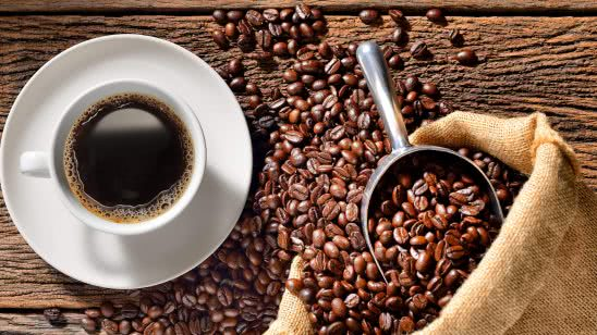 cup of coffee and roasted beans on wood table uhd 4k wallpaper